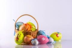 Huevos de Pascua en la cesta, aislada en el fondo blanco Foto de archivo