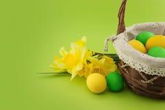 Huevos de Pascua en la cesta con el ramo de narciso amarillo Imagen de archivo libre de regalías
