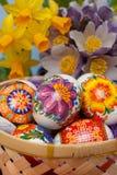 Huevos de Pascua en la cesta con las flores Fotos de archivo