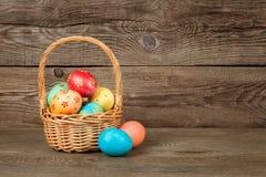 Huevos de Pascua en la cesta de tabla de madera Foto de archivo