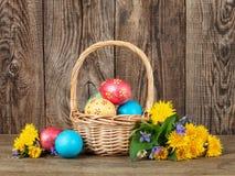 Huevos de Pascua en la cesta de tabla de madera imagenes de archivo