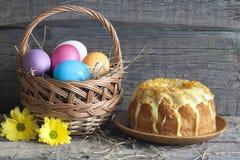 Huevos de Pascua en la cesta y la torta Imagenes de archivo