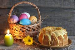 Huevos de Pascua en la cesta y la torta Fotos de archivo