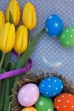 Huevos de Pascua en la jerarquía con los tulipanes amarillos Imágenes de archivo libres de regalías