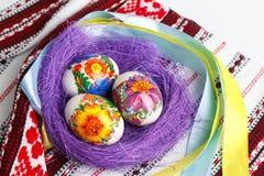 Huevos de Pascua en la jerarquía en la toalla del ornamento Fotografía de archivo