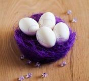 Huevos de Pascua en la jerarquía púrpura de la paja Imagen de archivo libre de regalías