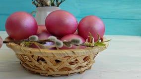 Huevos de Pascua en la rama de la cesta del tiroteo lento decorativo de la composición del sauce,