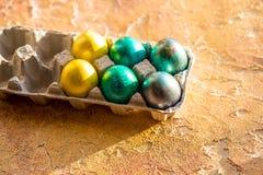 Huevos de Pascua en la tabla amarilla Fondo del día de fiesta Esquina de una bandeja de huevos coloridos Concepto feliz de Pascua Fotografía de archivo libre de regalías