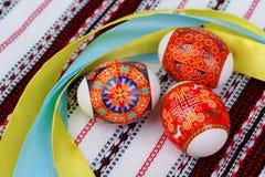 Huevos de Pascua en la toalla bordada Imagenes de archivo
