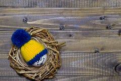Huevos de Pascua en los Emoticons de la jerarquía en sombreros hechos punto con los pom-poms Imágenes de archivo libres de regalías