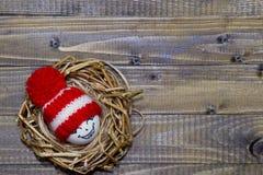 Huevos de Pascua en los Emoticons de la jerarquía en sombreros hechos punto con los pom-poms Imagen de archivo libre de regalías