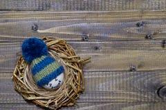 Huevos de Pascua en los Emoticons de la jerarquía en sombreros hechos punto con los pom-poms Foto de archivo libre de regalías