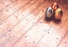 Huevos de Pascua en piso de madera fotos de archivo