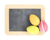 Huevos de Pascua en tablero vacío Imagen de archivo libre de regalías