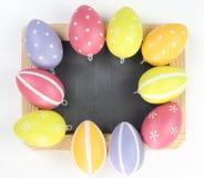 Huevos de Pascua en tablero vacío Imagen de archivo