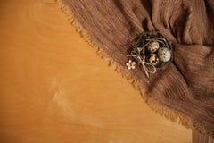Huevos de Pascua en textura de la tela y de la madera contrachapada de la arpillera del giro fotografía de archivo libre de regalías