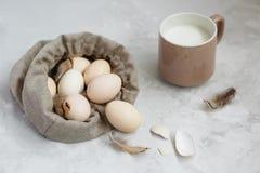 Huevos de Pascua en un bolso de la lona en un fondo gris fotos de archivo