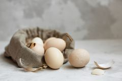 Huevos de Pascua en un bolso de la lona en un fondo gris fotografía de archivo libre de regalías