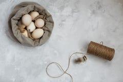Huevos de Pascua en un bolso de la lona en un fondo gris fotografía de archivo