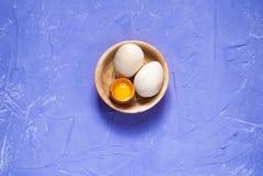 Huevos de Pascua en un plato de madera en un fondo púrpura, foto de archivo