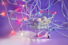 Huevos de Pascua en una carretilla de las compras Foto de archivo libre de regalías