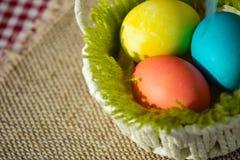 Huevos de Pascua en una cesta blanca foto de archivo