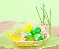 Huevos de Pascua en una cesta con las plumas amarillas Imágenes de archivo libres de regalías