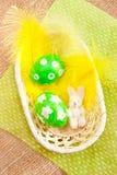 Huevos de Pascua en una cesta con las plumas amarillas Fotos de archivo libres de regalías