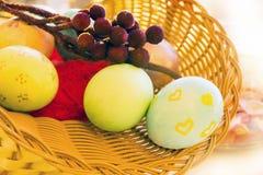 Huevos de Pascua en una cesta con una rama en Fotos de archivo