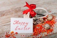 Huevos de Pascua en una cesta con una tarjeta pascua feliz Fotografía de archivo