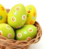 Huevos de Pascua en una cesta de la esquina inferior Imagen de archivo