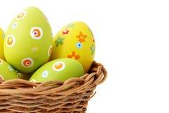 Huevos de Pascua en una cesta de la esquina izquierda Fotografía de archivo