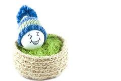 Huevos de Pascua en una cesta Emoticons en sombreros hechos punto con los pom-poms Imágenes de archivo libres de regalías