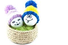 Huevos de Pascua en una cesta Emoticons en sombreros hechos punto con los pom-poms Imagen de archivo libre de regalías