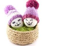 Huevos de Pascua en una cesta Emoticons en sombreros hechos punto con los pom-poms Fotografía de archivo
