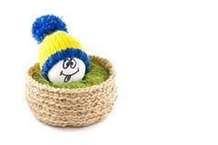 Huevos de Pascua en una cesta Emoticons en sombreros hechos punto con los pom-poms Fotos de archivo