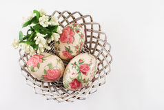 Huevos de Pascua en una cesta en blanco Fotografía de archivo