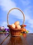 Huevos de Pascua en una cesta en la textura de madera en fondo del cielo azul Foto de archivo libre de regalías