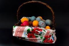 Huevos de Pascua en una cesta en un foco selectivo del fondo negro Fotos de archivo