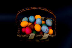 Huevos de Pascua en una cesta en un fondo negro Foto de archivo