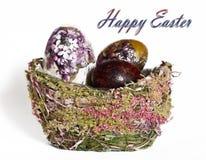 Huevos de Pascua en una cesta hecha de materiales naturales Imágenes de archivo libres de regalías