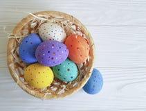 Huevos de Pascua en una cesta, paja, espacio pintado de madera de la primavera Imagen de archivo libre de regalías
