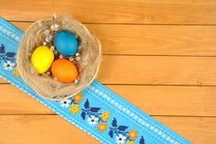 Huevos de Pascua en una cesta redonda con las ramitas del sauce Foto de archivo