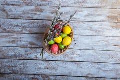 Huevos de Pascua en una cesta en una tabla de madera Fotografía de archivo libre de regalías