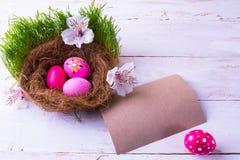 Huevos de Pascua en una jerarquía con las flores blancas fotografía de archivo libre de regalías