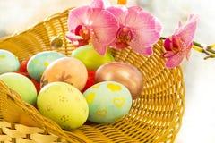 Huevos de Pascua en una salida del sol de la cesta Foto de archivo