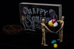 Huevos de Pascua felices de la primavera con dos maniquíes Foto de archivo