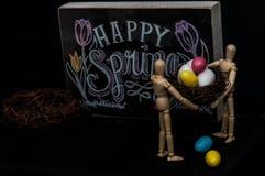 Huevos de Pascua felices de la primavera con dos maniquíes Fotos de archivo libres de regalías