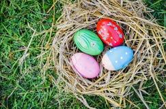 Huevos de Pascua festivos adornados coloridos de la tradición de los ahorros en hierba verde imagenes de archivo