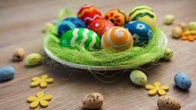 Huevos de Pascua grandes y pequeños en el cuenco en fondo de madera brillante metrajes